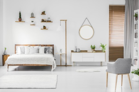Spacious designer white bedroom interior with wooden bed with bedding and pillows, night-table, small shelves above and modern armchair on the right. Real photo.
